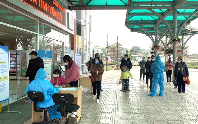 Người dân đến khám bệnh tại Bệnh viện Đa khoa tỉnh Yên Bái được hướng dẫn khai báo y tế, đo thân nhiệt và giữ khoảng cách an toàn theo đúng quy định của Bộ Y tế. (Ảnh: Thủy Thanh)