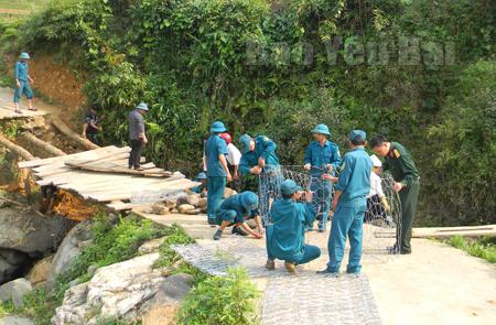 Cán bộ, chiến sỹ Ban Chỉ huy Quân sự huyện Trạm Tấu và lực lượng dân quân sửa chữa cầu cho người dân tại xã Hát Lừu.