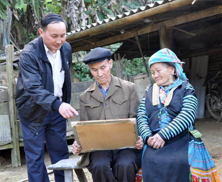 Già làng Tráng Nủ Cao (giữa) nâng niu tấm bằng khen được UBND huyện Trạm Tấu trao tặng vì đã có thành tích xuất sắc trong thực hiện Chỉ thị 03 của Bộ Chính trị năm 2016.