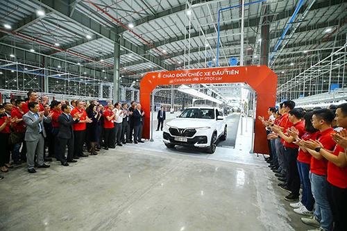 Các thành viên VinFast chào đón xe đầu tiên lăn bánh khỏi dây chuyền.