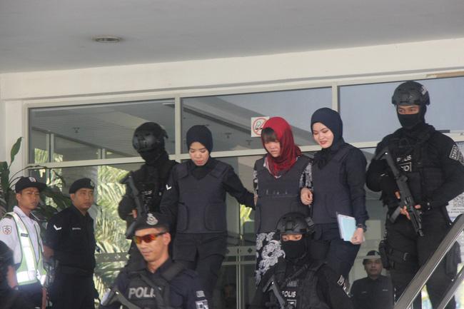 Cảnh sát dẫn giải Đoàn Thị Hương ra xe sau khi kết thúc phiên xét xử ngày 14/3.