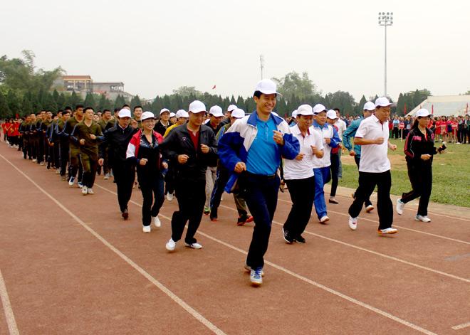 Lãnh đạo thành phố Yên Bái trao cờ lưu niệm cho các đoàn tham gia Ngày chạy Olympic.