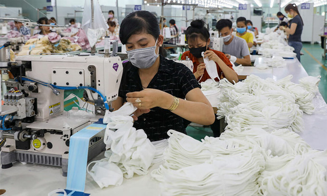 Workers manufacture masks in a factory in southern Long An Province on February 29, 2020.