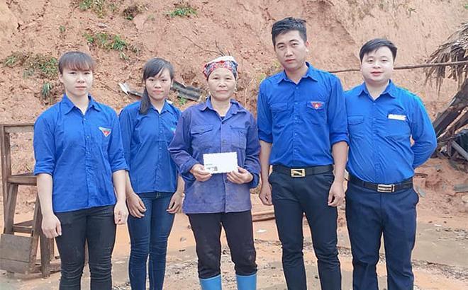 Anh Hà Đình Thao - Bí thư Đoàn xã Hưng Khánh (thứ 2, phải sang) trao tiền hỗ trợ cho hộ dân trên địa bàn bị thiệt hại do mưa bão.