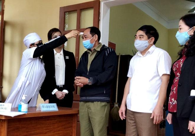 Cán bộ và người dân luôn được các lực lượng chức năng của huyện Yên Bình đo thân nhiệt