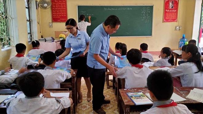 Cán bộ Bảo hiểm xã hội huyện Yên Bình phát tờ rơi tuyên truyền chính sách bảo hiểm y tế học sinh, sinh viên tại các trường học trên địa bàn huyện.