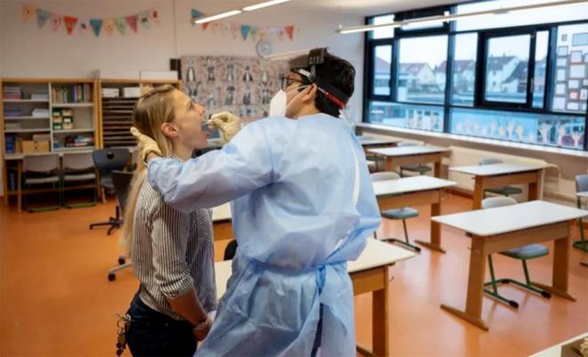 Một bác sĩ tiến hành lấy mẫu xét nghiệm cho một giáo viên. Ảnh minh họa: