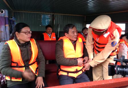 Lực lượng cảnh sát giao thông hướng dẫn người dân mặc áo phao khi đi tàu khách tại bến cảng Hương Lý, thị trấn Yên Bình, huyện Yên Bình.