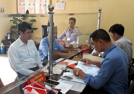 Cán bộ, công chức xã Việt Thành (Trấn Yên) tư vấn, giải quyết thủ tục hành chính cho người dân.