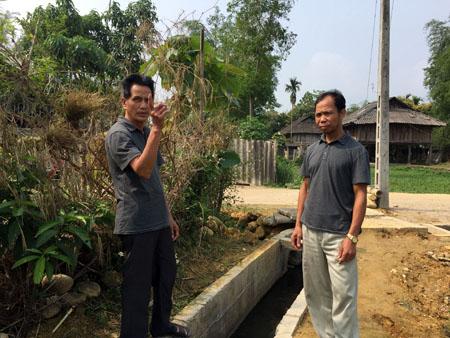Ông Đồng Văn Đức (bên trái) tuyên truyền cho người dân trong thôn  về việc khai thác, bảo vệ các công trình hạ tầng cơ sở.