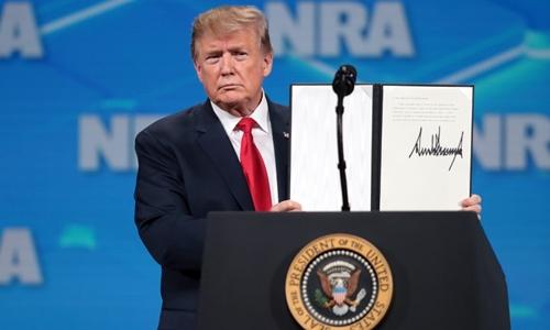 Trump cho khán giả xem văn bản ông ký để rút Mỹ khỏi ATT ngày 26/4.