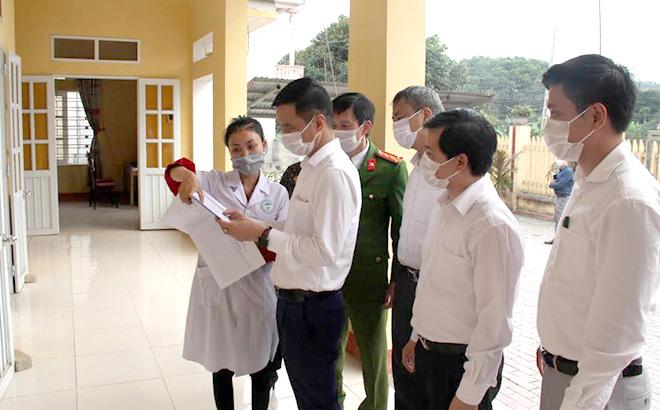 Đồng chí Dương Văn Tiến - Phó Chủ tịch UBND tỉnh kiểm tra sổ ghi chép khám, chữa bệnh tại xã Đại Minh, huyện Yên Bình.