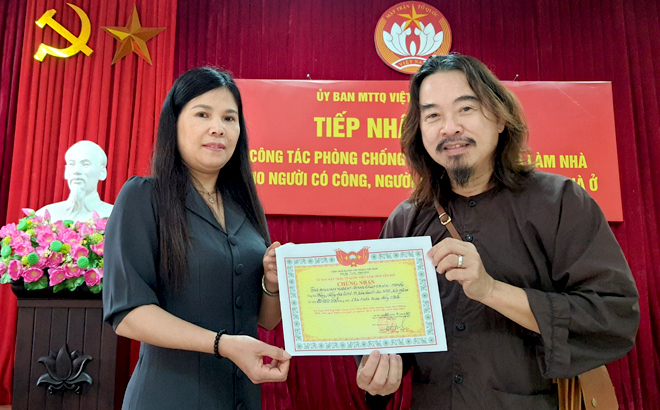 Nguyen Thi Bich Nhiem, Vice Chairwoman of the provincial Fatherland Front Committee, presents a certificate of William Hubert's donation to Nguyen Quang Truong on April 20 morning.