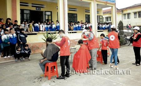 Đội tình nguyện viên chữ thập đỏ cắt tóc cho các em học sinh Trường THCS Dân tộc nội trú huyện Trấn Yên.