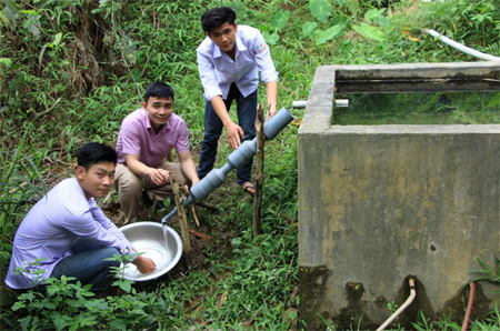 Em Hoàng Văn Cường, Hà Văn Mười và thầy giáo Nguyễn Văn Đức lắp đặt ống lọc nước tại nhà dân.
