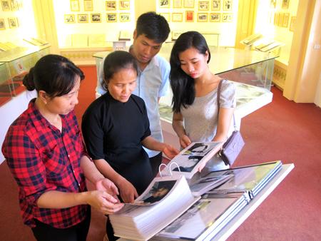 """Cô Chu Thị Tú Liên (giữa) và các bạn trẻ xem tập san """"Chủ tịch Hồ Chí Minh với sự nghiệp giáo dục"""" được trưng bày tại Khu tưởng niệm Chủ tịch Hồ Chí Minh thị xã Nghĩa Lộ."""