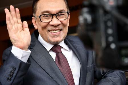 Chính trị gia Anwar Ibrahim vẫy tay chào người ủng hộ sau khi rời bệnh viện ở thủ đô Kuala Lumpur sáng 16-5.
