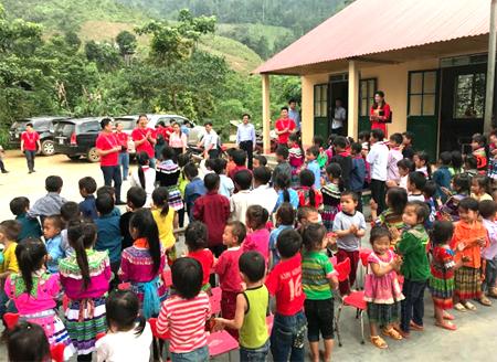 Ông Hiroshi Yokota và đại diện nhà phân phối Lê Bảo Minh (hai người áo đỏ đứng vỗ tay) hát cùng học trò bản Ba Khuy (Văn Yên, Yên Bái).