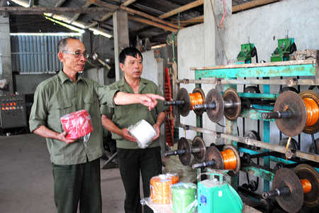 Cựu chiến binh Nguyễn Hùng Cường (bên trái)  giới thiệu hệ thống máy cuộn dây khâu, dây buộc.
