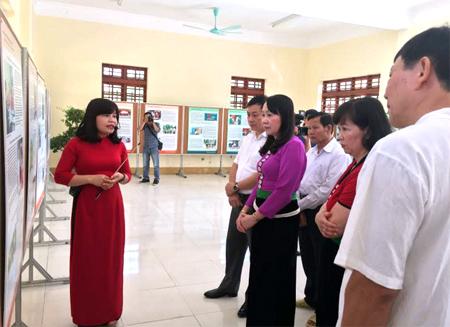Các đại biểu thăm quan triển lãm ảnh và nghe hướng dẫn viên Bảo tàng Hồ Chí Minh giới thiệu về triển lãm.