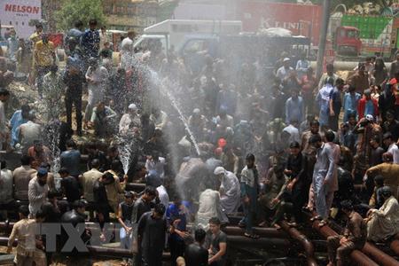 Người dân giải nhiệt tại hệ thống ống cấp nước ở Karachi, Pakistan ngày 22-5.