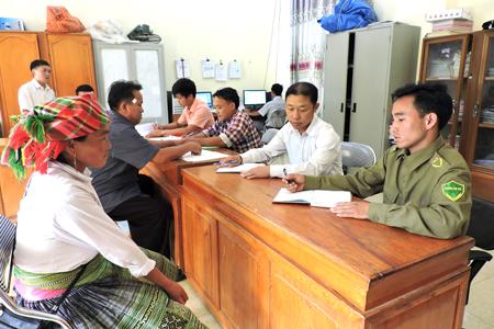 Cán bộ bộ phận một cửa xã Bản Công, huyện Trạm Tấu giúp người dân giải quyết TTHC. (Ảnh: Lộc Chầm)