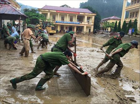 Tuổi trẻ Công an huyện Mù Cang Chải giúp nhân dân khắc phục hậu quả mưa lũ.