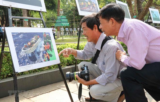 Các đại biểu và người dân thưởng lãm các tác phẩm ảnh nghệ thuật.