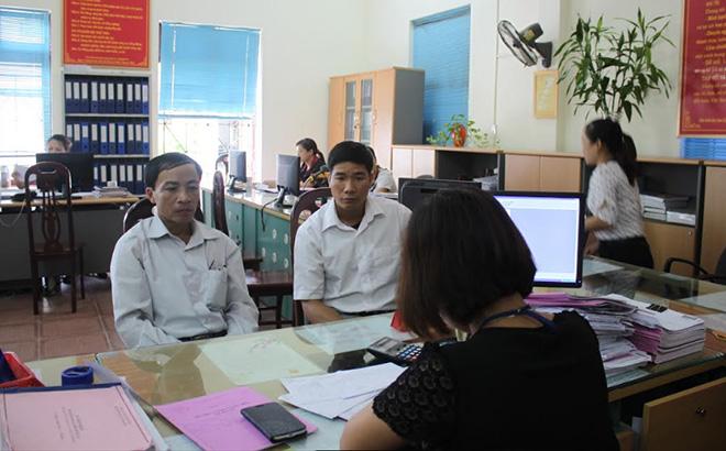 Cán bộ Chi cục Thuế khu vực Trấn Yên - Văn Yên hướng dẫn thủ tục hành chính cho người nộp thuế.