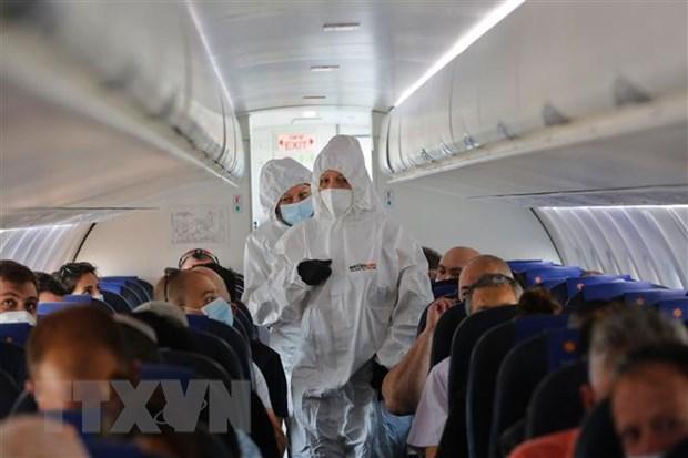 Tiếp viên hàng không mặc quần áo bảo hộ phòng lây nhiễm COVID-19 trên máy bay.