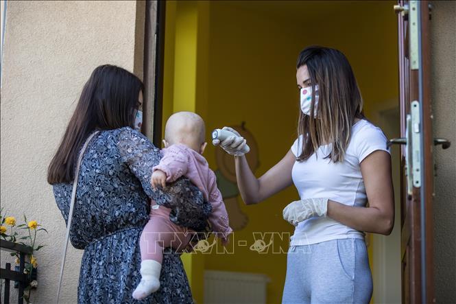 Kiểm tra thân nhiệt cho trẻ nhỏ tại nhà trẻ ở Krakow, Ba Lan ngày 11/5/2020 trong bối cảnh dịch COVID-19 lan rộng.