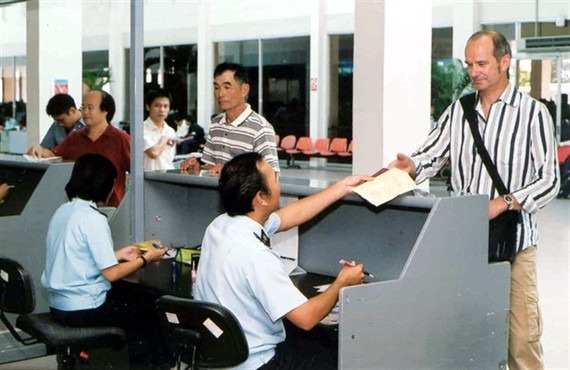 A customs official conducts immigration procedures for a foreigner at Tan Son Nhat airport in HCM City.
