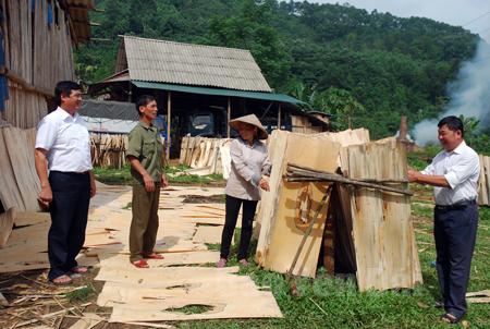 Anh Nguyễn Văn Thuấn (thứ hai từ trái sang) và lãnh đạo Hội Cựu chiến binh, Hội Nông dân xã trao đổi với người lao động làm việc tại xưởng chế biến gỗ.