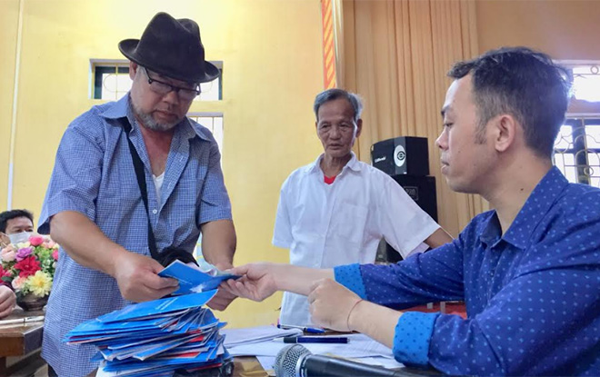 Người dân thị trấn Yên Thế nhận tiền hỗ trợ do ảnh hưởng dịch bệnh Covid-19.