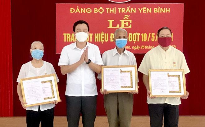 Bí thư Huyện ủy Yên Bình An Hoàng Linh trao Huy hiệu Đảng cho các đảng viên tại Đảng bộ thị trấn Yên Bình.