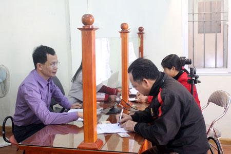 Cán bộ bộ phận một cửa Sở Giao thông - Vận tải hướng dẫn người dân làm thủ tục đổi giấy phép lái xe.