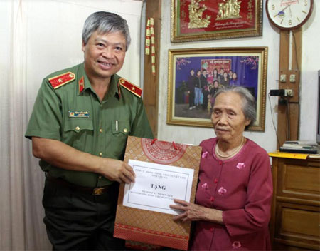 Đồng chí Đặng Trần Chiêu - Giám đốc Công an tỉnh thăm và tặng quà cụ Lương Thị Len, vợ liệt sỹ.