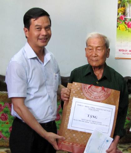 Đồng chí Dương Văn Tiến - Phó Chủ tịch UBND tỉnh tặng quà ông Nguyễn Văn Hứ,thị trấn Mù Cang Chải.