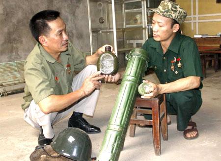 Cựu chiến binh Nguyễn Văn Kim (bên phải) cùng đồng đội là cựu chiến binh Lê Huy Tâm ôn lại kỷ niệm bên các kỷ vật một thời.