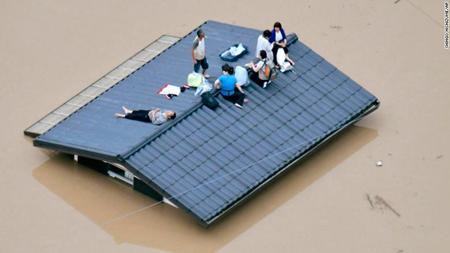 Người dân trèo lên mái nhà chờ được giải cứu.