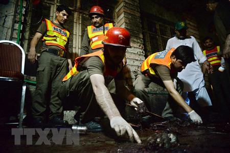 Nhân viên cứu hộ Pakistan làm nhiệm vụ tại hiện trường vụ đánh bom đẫm máu ở Peshawar ngày 10/7.