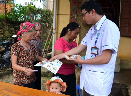 Cán bộ y tế xã An Lương, huyện Văn Chấn phát tờ rơi tuyên truyền phòng, chống bệnh dại cho nhân dân.