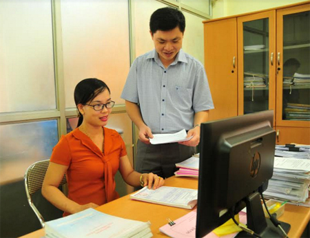 Cán bộ Chi cục Thuế huyện Trấn Yên trao đổi công tác thu liên quan đến khối doanh nghiệp.