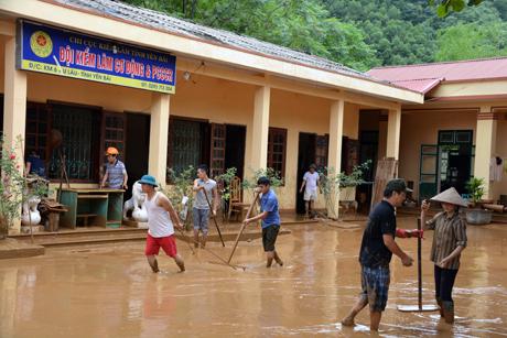 Cán bộ, nhân viên Đội Kiểm lâm Cơ động và PCCCR cùng nhân dân thôn Đắng Con vận chuyển bùn, đất ra khỏi khu vực sân trụ sở đơn vị.