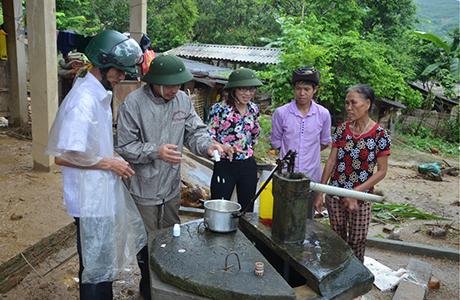 Lãnh đạo Sở Y tế hướng dẫn người dân xã Sơn Lương, huyện Văn Chấn vệ sinh khử khuẩn nguồn nước sinh hoạt.