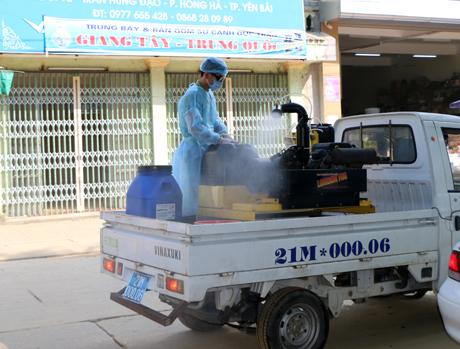 Cán bộ Trung tâm Y tế thành phố phun thuốc khử khuẩn tại phường Hồng Hà, thành phố Yên Bái.