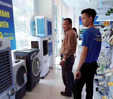 Nhân viên bán hàng tại Siêu thị Trần Anh giới thiệu sản phẩm điều hòa cho khách hàng.