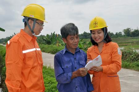 Công nhân ngành điện tuyên truyền tiết kiệm điện mùa nắng nóng cho người dân.