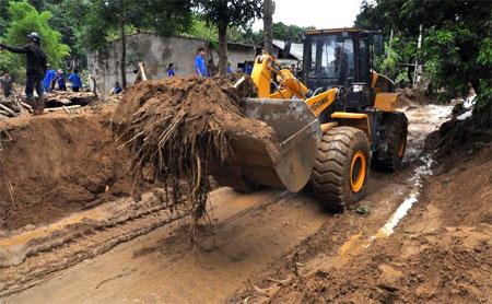 Các lực lượng đang khẩn trương san, hót, gạt bùn đất để khôi phục giao thông tuyến đường đi xã Nậm Mười, huyện Văn Chấn.