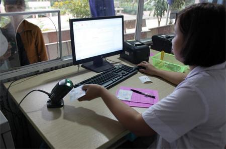 Cán bộ tại Bộ phận tiếp đón bệnh nhân Trung tâm Y tế huyện Trấn Yên quét mã thẻ BHYT cho bệnh nhân.